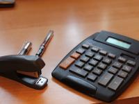 Calculator, stapler and pens on a desk