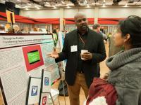 Presenter and visitor conversing at a research symposium
