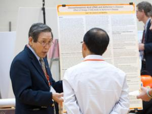Faculty member discussing research at a symposium